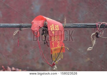 a red fabric on wooden railings. word on cloth meaning happy.