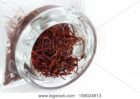 close up image of Saffron in a thick glass jar on a white background copy space to the right