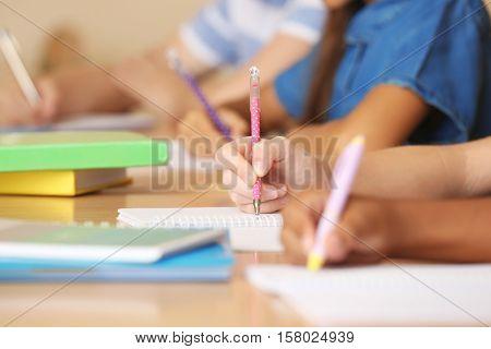 Children hands writing in copybooks, closeup
