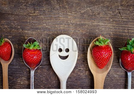 Strawberries on spoons and wooden spoon with smiley face. Leadership uniqueness independence initiative strategy dissent think different success summer happiness smile positivity concept.