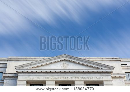 Motion blur clouds illustrating time moving quickly past front of Dirksen Senate office building Washington DC