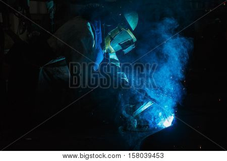 Welder of Metal Welding with sparks in industry steel weld