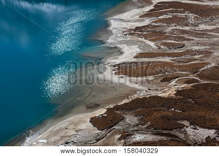 Aerial View Of Gokyo Lake Turquoise Waters And White Sand Beach Shore Line. Beautiful Lakeside Of Th