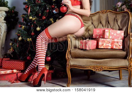 Beautiful sexy Santa Clause in elegant panties stockings and bra. Fashion portrait of model girl indoors with christmas tree. Cute woman in lace red lingerie. Female ass in underwear. Naked body