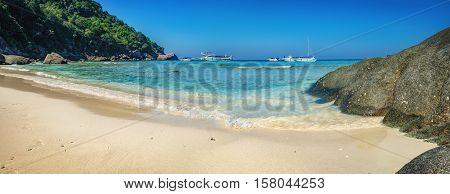 Phang Nga, Thailand - January 4, 2016: Foamy waves on the Koh Similan No.8 Island in Similan National park Andaman Sea Thailand. Beautiful landscape with the rock and tourist boats.