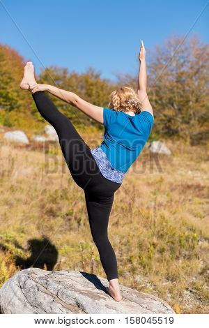 Young woman standing on one leg on rock and holding the other in the air in yoga pose
