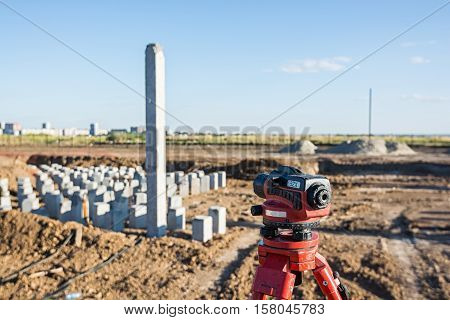 Theodolite in front of piles field on construction site