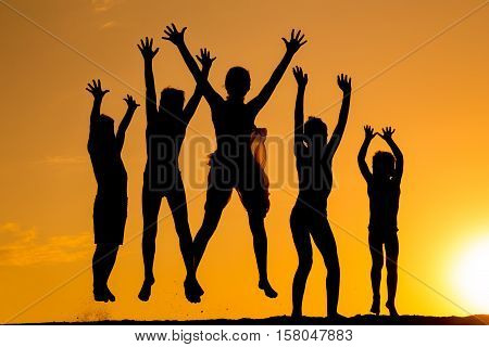 silhouette of five happy jumping kids against sunset