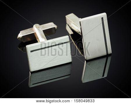 beautiful silver cufflinks on black back ground.
