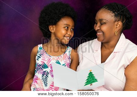 Close up portrait of African mother reading christmas card to little daughter against dark background.