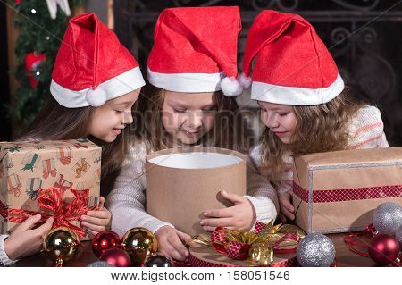 Funny toddler girls waiting for surprise from gift present box and making wish ready to celebrate New Year and Christmas at home