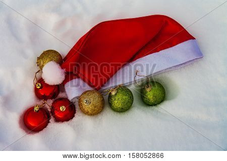 Composition with Santa Claus red hat and Christmas decorations on snow background
