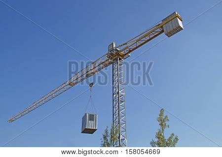 Crane at a construction site with a container suspended, italy