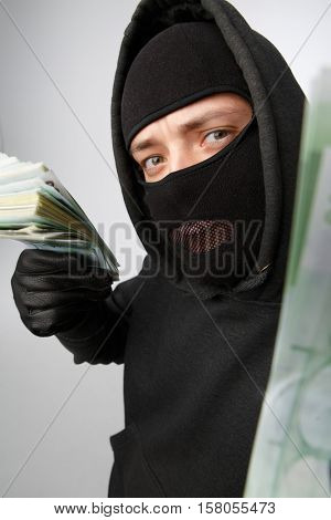Robber in mask holding banknotes