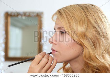 Professional makeup artist applying lip gloss