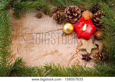 Christmas decoration with red Advent candle and fir branch frame, top view with copy space on wood. Christmas ornaments border with fir tree branches and decoration.