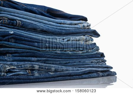 Stack of old and worn blue jeans over a white background