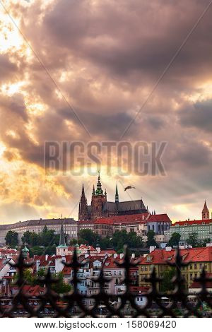 Panoramic view of St. Vitus Cathedral and Castle in Prague, Czech Republic. Beautiful dramatic sunset sky with rays of making their way through clouds.
