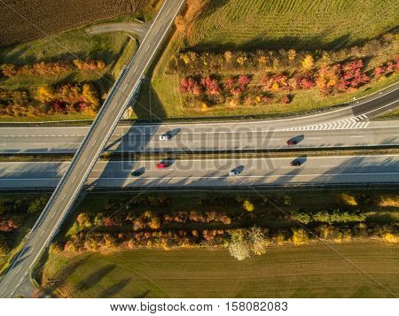 Aerial view of a highway amid fields with cars on it