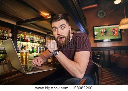 Shocked astonished young man drinking beer and using laptop in bar