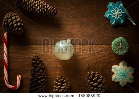 Beautiful christmas frame decoration from peppermint candy cane stick christmas ball candle showflake shaped and patterned bisquit cookies fir cones and pinecones at brown wooden background.