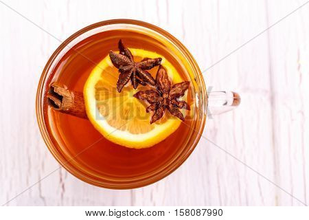 Cup Of Tea With Cinnamon, Lemon And Other Seasonings Stands On White Table