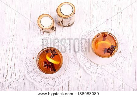 Cups Of Christmas Tea And Candles Stand On White Table
