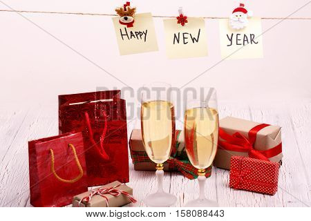 Cards With Lettering 'happy New Year' Hang Over Champagne Flutes And Present Boxes