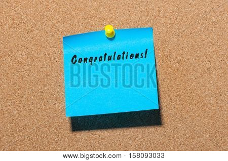 Congratulations - inscription on blue sticker pinned to cork notice board. With empty space for text.
