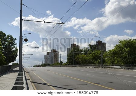 City boulevard with trolley wires and fluffy clouds