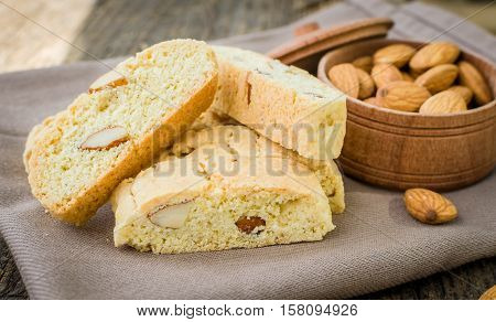 Italian cantuccini cookies with almonds. Traditional italian almond cookies biscotti on old wooden background. Homemade Almond cookies on wooden table. Delicious cookies biscotti. Selective focus.