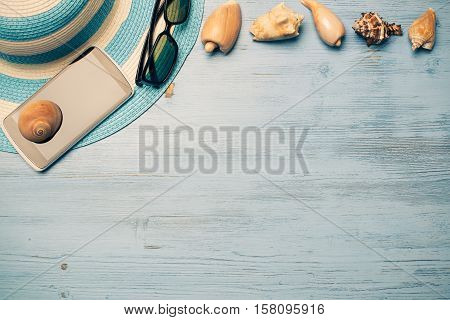 Straw hat sunglasses smartphone and photocamera among sea shells and stones on wooden surface