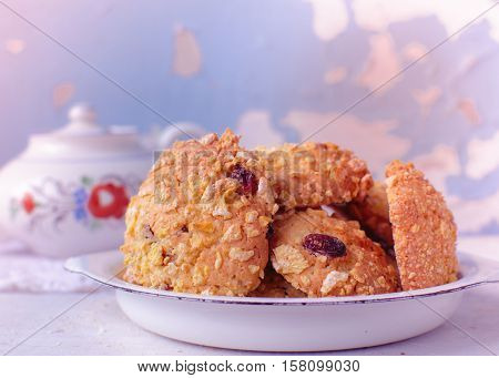 Homemade cornflakes and raisins cookies with tea pot on old wall background. Freshly baked corn flake cereal cookies in rustic style. Selective Focus. Toned image.