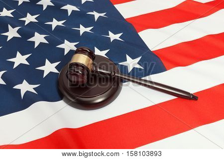Close up studio shot of a judge gavel and a soundboard over flag of USA