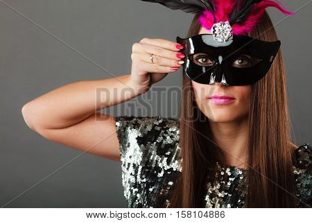 Holidays people and celebration concept. Closeup woman face with carnival venetian mask sequin evening dress on gray background.
