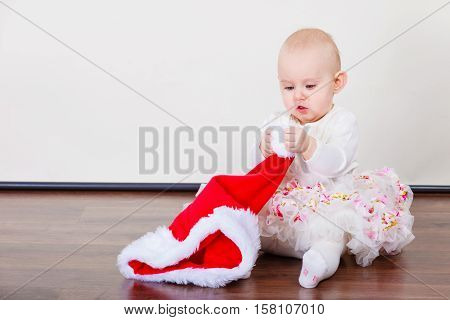 Family christmas people concept. Little baby girl sitting on floor. Cute toddler holding red santa claus cap.