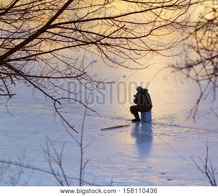 Unidentified fisherman fishing on the ice of a frozen river.