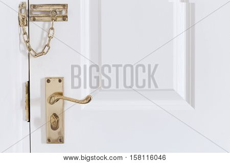 golden metal handle and chain on the white front entrance door