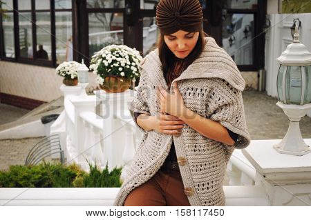 Outdoor portrait of a young woman dressed in fashion hat and cardigan, cute autumn outfit