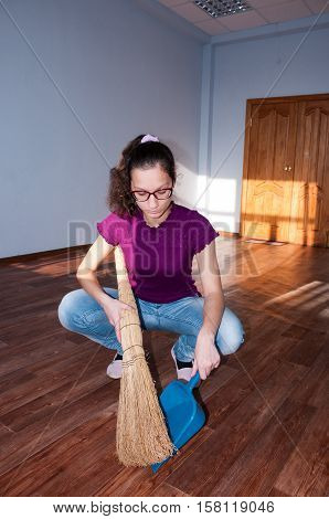 Girl With Glasses In Sweeping Floor Apartment  Девушка в очках подметает в квартире пол