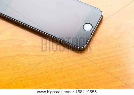 Close Up Of Cellphone Lying On Wooden Table