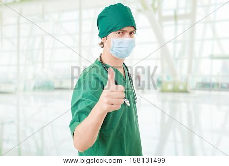 Happy male doctor showing thumbs up, at the hospital
