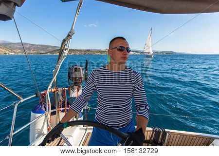 Skipper at the helm controls of a sailing yacht.