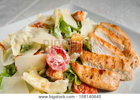Caesar salad with fried chicken meat, free space. Restaurant serving of side dish with fried poultry and fresh vegetables. Mediterranean cuisine, appetizer, menu concept