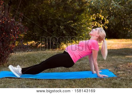 Young pregnant stretching outdoor, side view. Expectant woman doing fitness exercise on green meadow background. Health and body care, yoga, leisure, healthy lifestyle concept