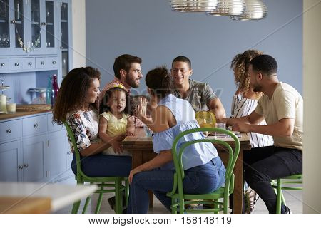 Friends with a child sit talking around a dining room table