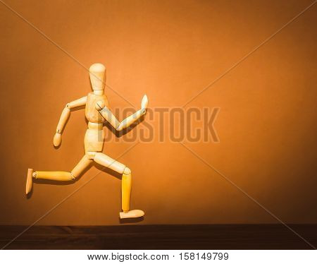 The figure of wooden man, running on wooden background