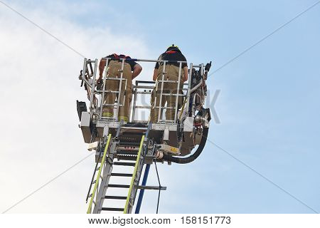 Firemen on a crane looking for a fire. Working professions. Horizontal