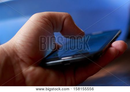 Closeup of young boys hand using smartphone with blurred blue background