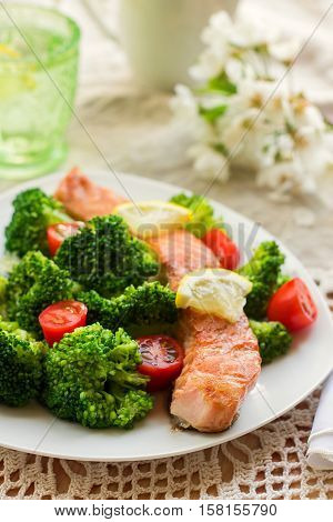 Salmon teriyaki served with broccoli tomatoes and lemon